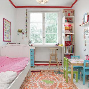 Immagine di una cameretta per bambini da 4 a 10 anni eclettica di medie dimensioni con pareti bianche e pavimento in legno verniciato