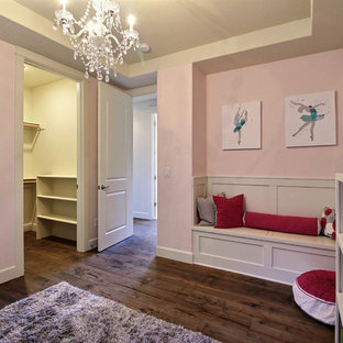 Immagine di un'ampia cameretta per bambini da 4 a 10 anni stile americano con pareti rosa, pavimento in legno massello medio e pavimento marrone