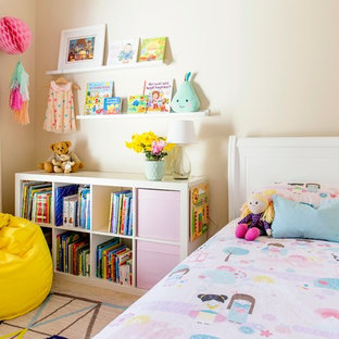 This is an example of a small transitional toddler room for girls in Melbourne with beige walls and carpet.