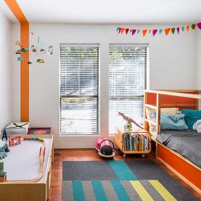 Kids' room - mid-century modern gender-neutral medium tone wood floor kids' room idea in Austin with multicolored walls