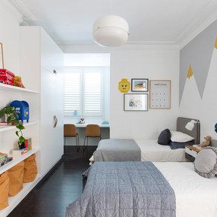 Réalisation d'une grand chambre d'enfant de 4 à 10 ans design avec un mur blanc, un sol en bois peint et un sol noir.