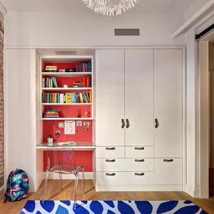 Cette image montre une petit chambre neutre de 4 à 10 ans urbaine avec un bureau, un mur rouge et un sol en bois clair.
