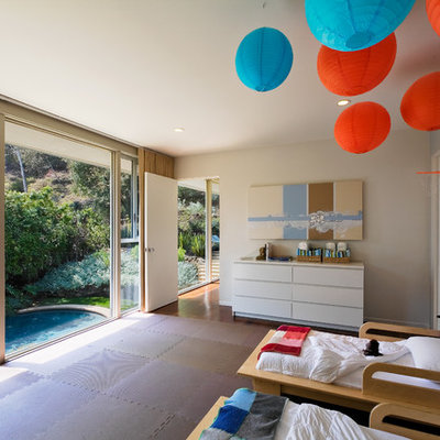 Example of a mid-century modern gender-neutral kids' room design in Los Angeles with gray walls