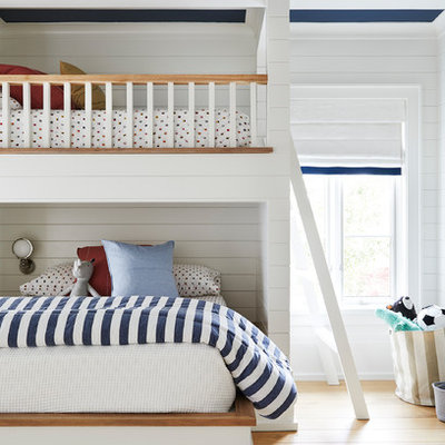 Beach style gender-neutral light wood floor kids' room photo in Dallas with white walls