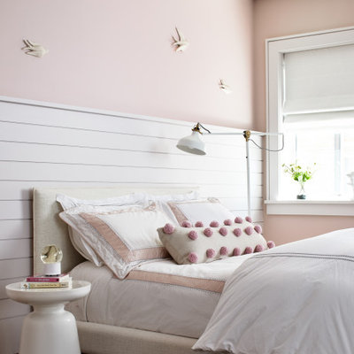 Example of a large transitional girl medium tone wood floor and brown floor kids' room design in Los Angeles with pink walls