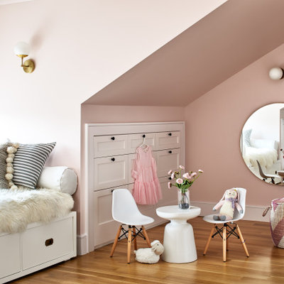 Large transitional girl medium tone wood floor and brown floor kids' room photo in Los Angeles with pink walls