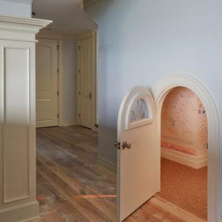 Esempio di una cameretta per bambini da 4 a 10 anni mediterranea di medie dimensioni con pareti beige, pavimento in laminato e pavimento marrone