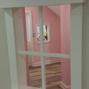 Idee per una piccola cameretta per bambini da 4 a 10 anni american style con pareti rosa, pavimento in laminato e pavimento marrone