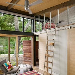 Modelo de dormitorio infantil actual con paredes blancas y suelo de madera en tonos medios