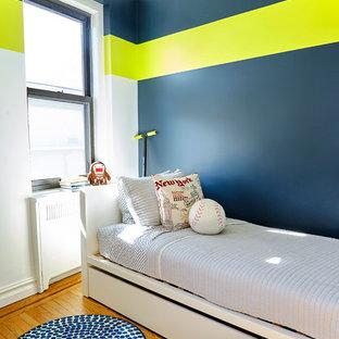 Modern inredning av ett litet pojkrum kombinerat med sovrum och för 4-10-åringar, med mellanmörkt trägolv och flerfärgade väggar
