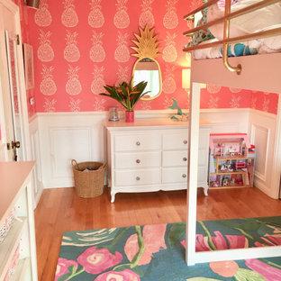 Ispirazione per una cameretta per bambini da 4 a 10 anni tropicale di medie dimensioni con pareti rosa, pavimento in legno massello medio e carta da parati