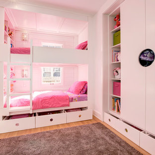 This is an example of a small contemporary children's room for girls in Indianapolis with light hardwood flooring and white walls.