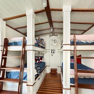 Foto på ett litet maritimt barnrum kombinerat med sovrum, med mellanmörkt trägolv