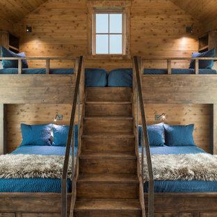 Immagine di una cameretta per bambini stile rurale con pareti marroni, pavimento in legno massello medio, pavimento marrone, soffitto in legno e pareti in legno