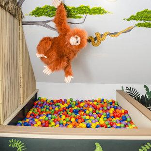 Idéer för stora tropiska könsneutrala barnrum kombinerat med lekrum, med flerfärgade väggar och mellanmörkt trägolv