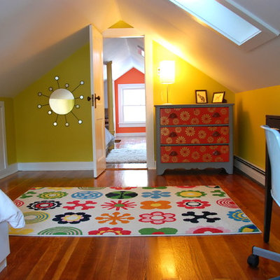Example of an eclectic gender-neutral medium tone wood floor kids' study room design in New York with yellow walls