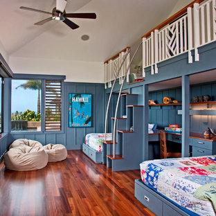 Kolonialstil Kinderzimmer mit Schlafplatz, blauer Wandfarbe, braunem Holzboden und braunem Boden in Hawaii