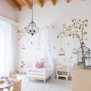 Esempio di una cameretta per bambini da 1 a 3 anni stile marino di medie dimensioni con pareti rosa, parquet chiaro e pavimento beige