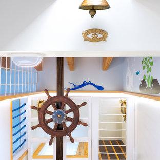 Idee per una grande cameretta per bambini da 4 a 10 anni stile marino con pareti blu e parquet chiaro