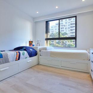 Idéer för att renovera ett vintage könsneutralt barnrum kombinerat med sovrum och för 4-10-åringar, med vita väggar och ljust trägolv