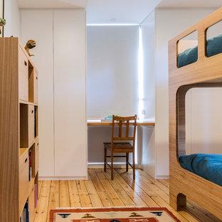 Exempel på ett litet minimalistiskt pojkrum kombinerat med sovrum och för 4-10-åringar, med vita väggar, plywoodgolv och brunt golv