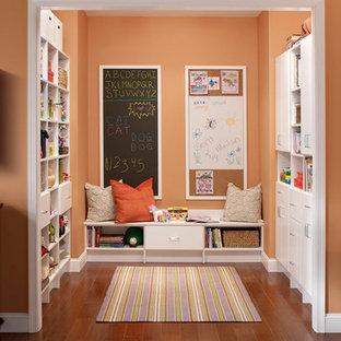 Aménagement d'une grande chambre d'enfant de 1 à 3 ans moderne avec un mur orange, un sol en bois foncé et un sol marron.