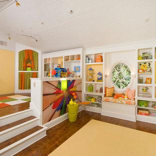 Immagine di una grande cameretta per bambini da 4 a 10 anni tradizionale con pareti gialle e pavimento in legno massello medio