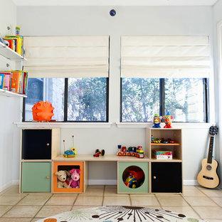 Idéer för att renovera ett mellanstort funkis könsneutralt barnrum kombinerat med lekrum, med vita väggar och travertin golv