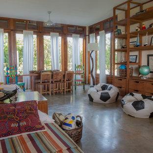 Foto di un'ampia cameretta per bambini da 4 a 10 anni tropicale con pareti beige e pavimento in cemento