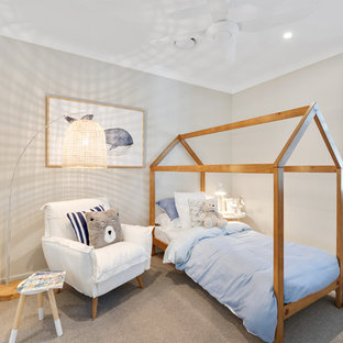 This is an example of a beach style kids' room for boys in Brisbane with grey walls, carpet and beige floor.