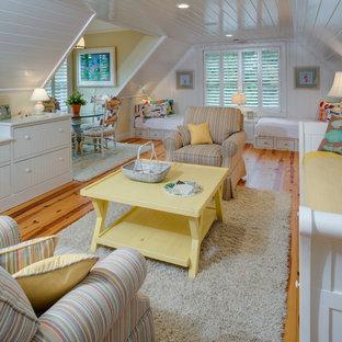 Idéer för stora maritima könsneutrala barnrum kombinerat med sovrum och för 4-10-åringar, med vita väggar, mellanmörkt trägolv och brunt golv