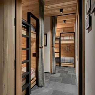 На фото: большая нейтральная детская в стиле рустика с спальным местом, бежевыми стенами, полом из сланца, черным полом и деревянными стенами для подростка