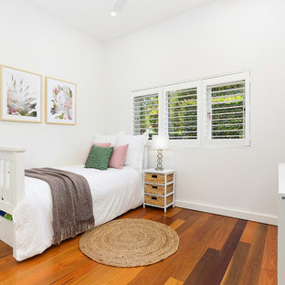 Design ideas for a mid-sized beach style kids' bedroom for kids 4-10 years old and girls in Sydney with white walls, medium hardwood floors and brown floor.