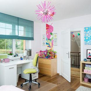 Idéer för eklektiska flickrum kombinerat med skrivbord och för 4-10-åringar, med vita väggar och mellanmörkt trägolv