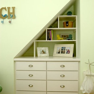 Example of a minimalist medium tone wood floor kids' room design in New York with green walls