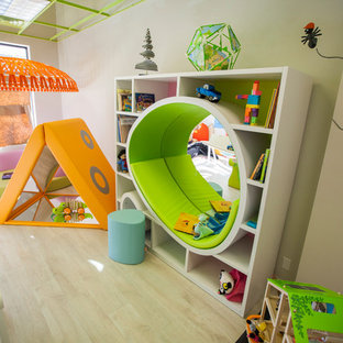 Large minimalist gender-neutral light wood floor playroom photo in Omaha with white walls