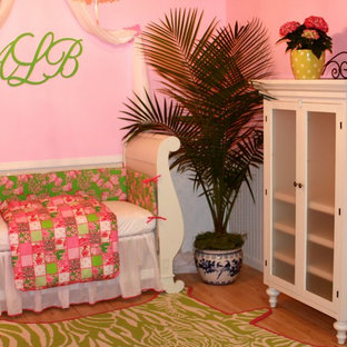Eclectic girl medium tone wood floor kids' room photo in Miami with pink walls