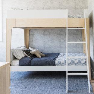 На фото: маленькая детская в скандинавском стиле с спальным местом, светлым паркетным полом, коричневым полом, кессонным потолком и обоями на стенах для ребенка от 4 до 10 лет, мальчика с
