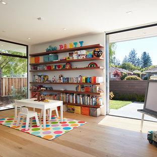 Exemple d'une chambre d'enfant de 1 à 3 ans rétro avec un mur blanc et un sol en bois clair.