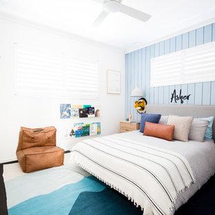 Exempel på ett modernt pojkrum, med blå väggar, heltäckningsmatta och svart golv
