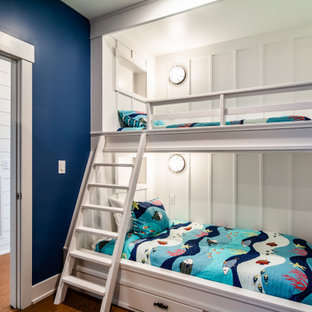 Mid-sized beach style gender-neutral medium tone wood floor and brown floor kids' room photo in Other with blue walls