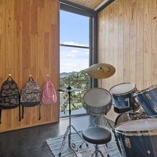 Immagine di una piccola cameretta per bambini da 4 a 10 anni eclettica con pareti marroni, pavimento in cemento e pavimento nero