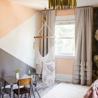 Medium sized classic children's room for girls in Denver with grey walls, laminate floors and grey floors.
