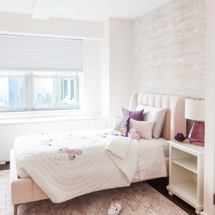 Inspiration for a mid-sized contemporary girl medium tone wood floor and brown floor kids' room remodel in New York with pink walls