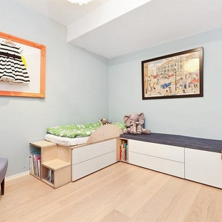 Modelo de dormitorio infantil de 1 a 3 años, minimalista, pequeño, con paredes azules y suelo de madera clara