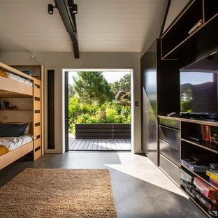 Стильный дизайн: нейтральная детская в современном стиле с спальным местом, белыми стенами, бетонным полом и серым полом - последний тренд