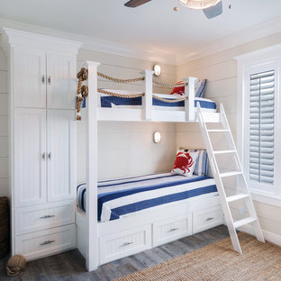 Inspiration pour une chambre d'enfant marine avec un mur beige et un sol en bois foncé.