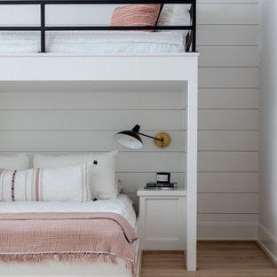 Foto di un'ampia cameretta per bambini tradizionale con pareti bianche, parquet chiaro, pavimento marrone, soffitto a volta e pareti in perlinato