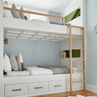 Idéer för att renovera ett maritimt barnrum kombinerat med sovrum, med blå väggar, mellanmörkt trägolv och brunt golv