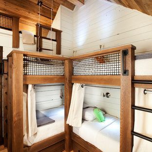 Mountain style gender-neutral medium tone wood floor and brown floor kids' bedroom photo with white walls